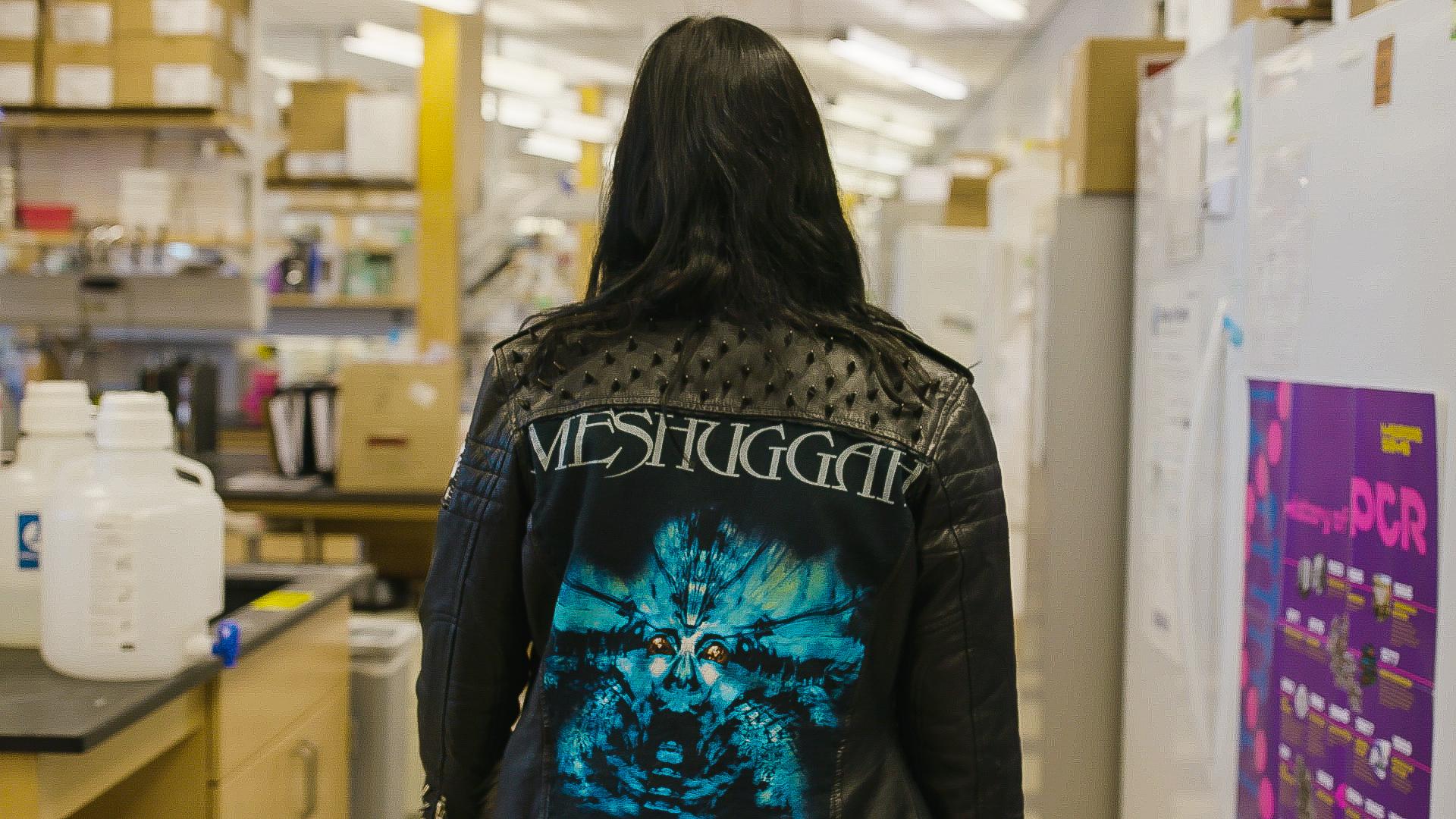 Women in metal jacket walking in lab